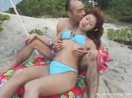 Hot Asian milf in a blue bikini sucks cock and rides it hard outdoors.