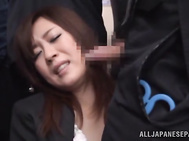 Beautiful Japanese office chick Nana Aoyama gets her big tits attacked by horny dudes in a public place.